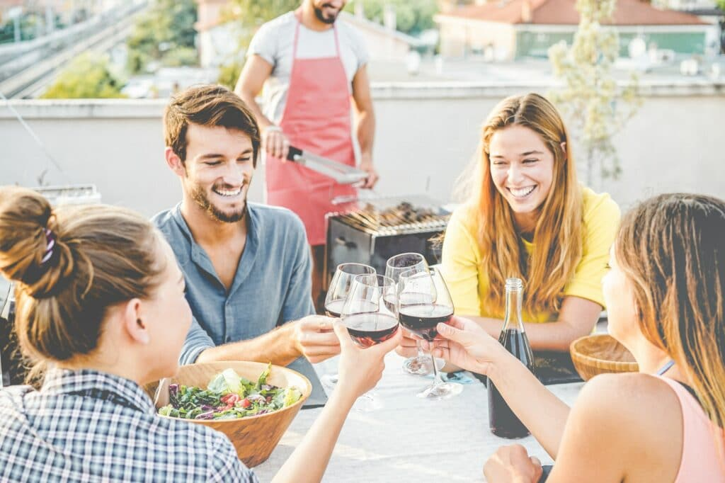 Happy friends cheering with red wine at barbecue dinner party